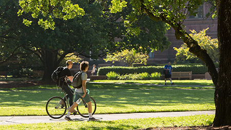 Students walking and biking through campus